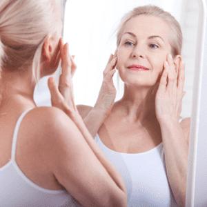 vrouw van middelbare leeftijd kijkt in spiegel
