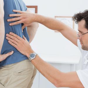arts onderzoekt rug van patiënt