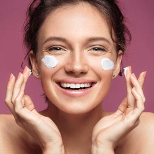 une fille se barbouille de crème sur le visage