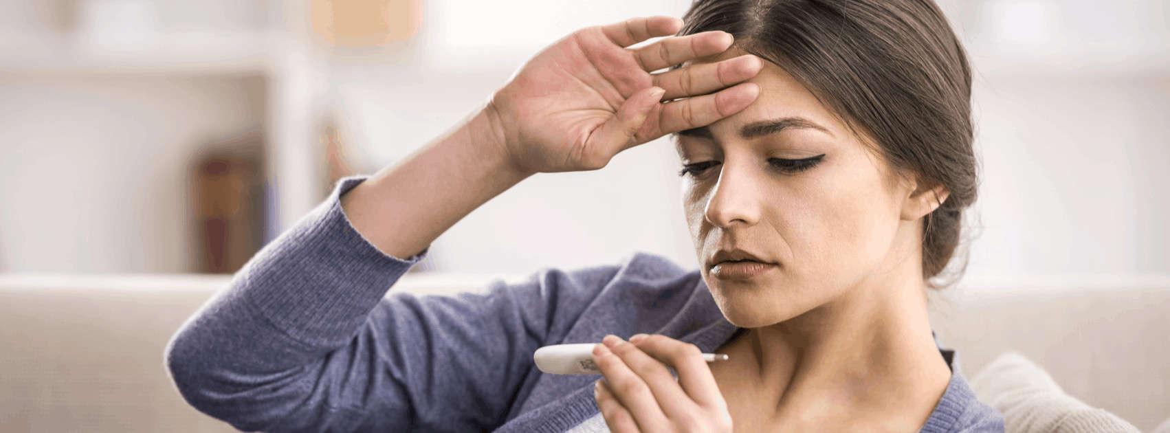 jonge vrouw kijkt op koortsthermometer
