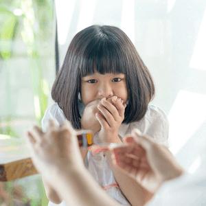 meisje houdt hand voor de mond als moeder haar een medicijn wil geven