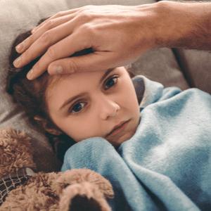 petite fille malade sur le canapé sous une couverture