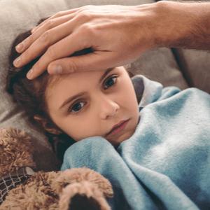 ziek klein meisje op bank onder een deken