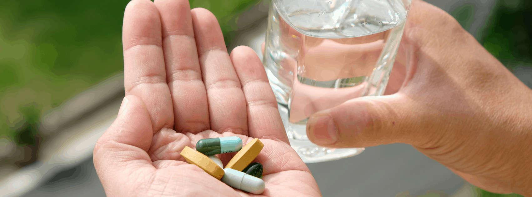 handen met medicijnen en glas water