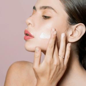 vrouw brengt creme aan op haar gezicht