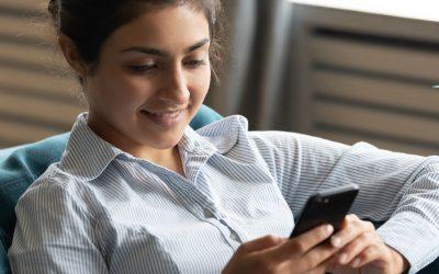 jonge vrouw kijkt lachend op haar smartphone