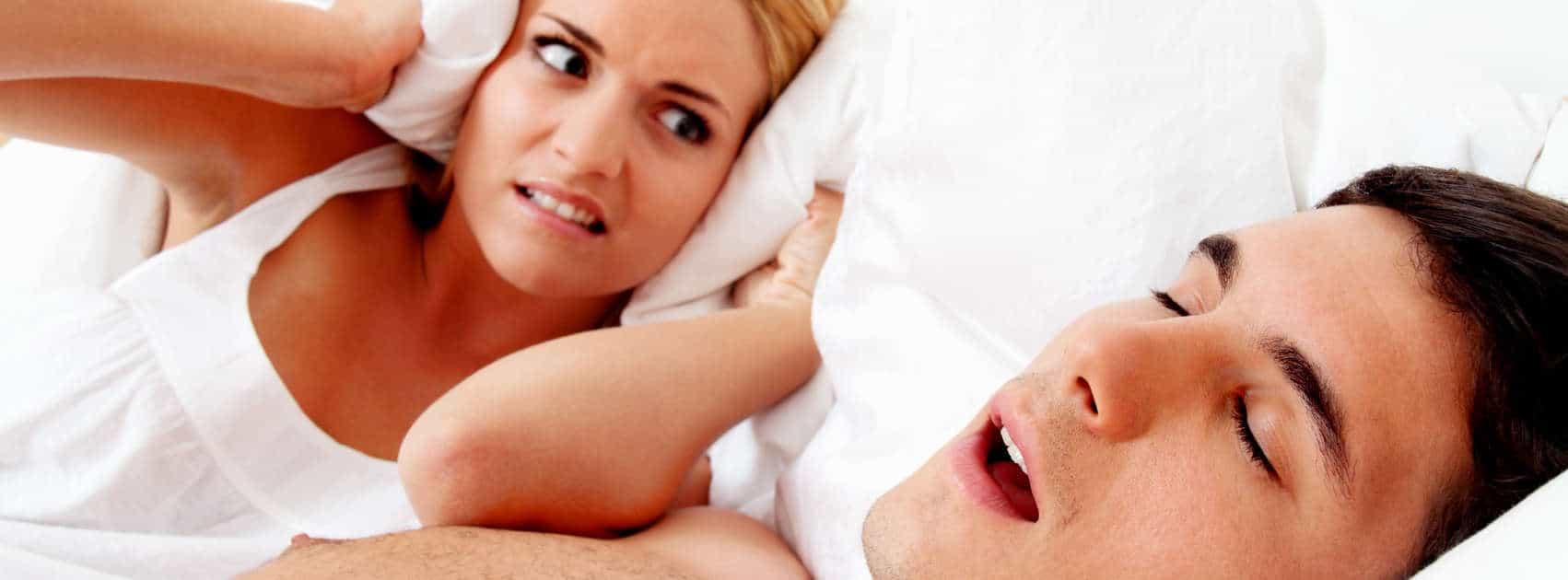 femme diabolique à côté d'un homme qui ronfle au lit