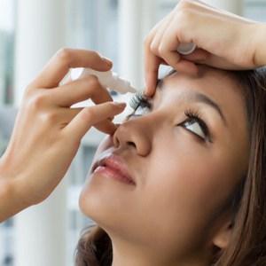 vrouw gebruikt oogdruppels