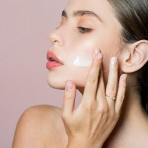 une femme met de la crème sur son visage