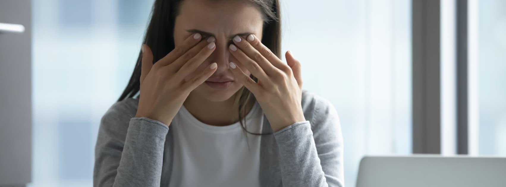 vrouw achter laptop wrijft in haar ogen