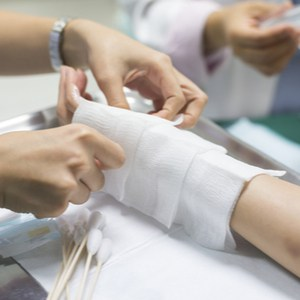 le médecin applique des pansements sur le bras du patient