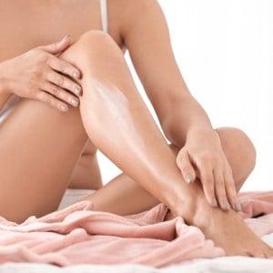 une femme s'enduit de crème sur le corps