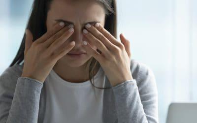 une femme derrière un ordinateur portable se frotte les yeux
