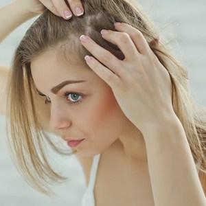 nerveus meisje in de spiegel kijken naar haar hoofdhuid