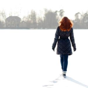 Vrij roodharig meisje dat op bevroren meer loopt en voetpad maakt