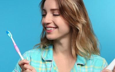 Jonge vrouw kiezen tussen handmatige en elektrische tandenborstels op kleur achtergrond