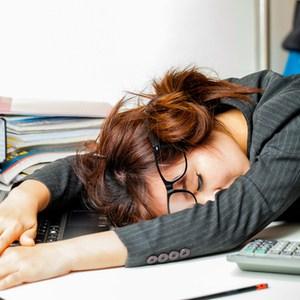 vrouw slaapt met hoofd op bureau