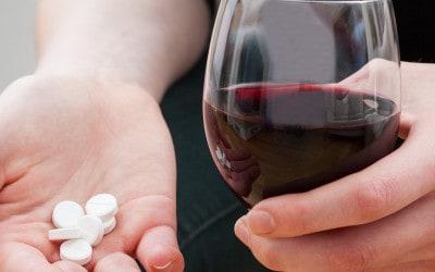 vrouw met glas wijn en medicijnen
