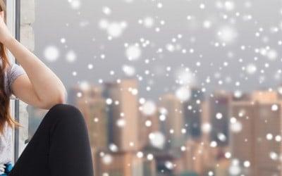 Adolescente mignonne triste et malheureuse assise sur la fenêtre sur le fond de la ville et de la neige