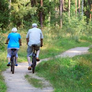 couple de personnes âgées faisant du vélo à la campagne
