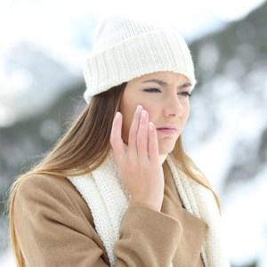 Close-up schoonheid portret van een lachende halfnaakte vrouw gezicht crème toe te passen en op zoek geïsoleerd op een witte achtergrond