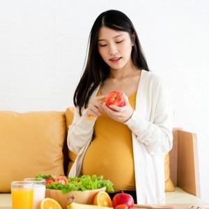 zwangere vrouw achter tafel met fruit