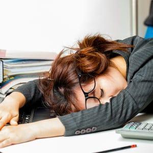femme dormant avec la tête sur le bureau