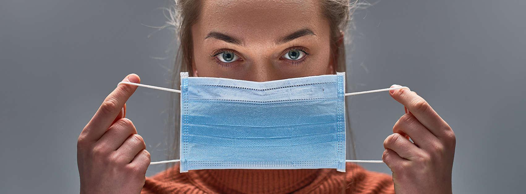 Gezonde vrouw met behulp van medisch beschermend masker voor bescherming van de gezondheid