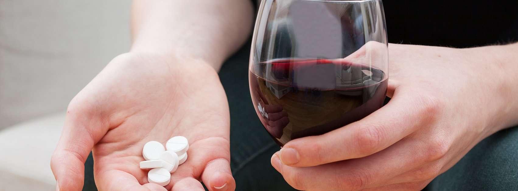 femme avec un verre de vin et des médicaments