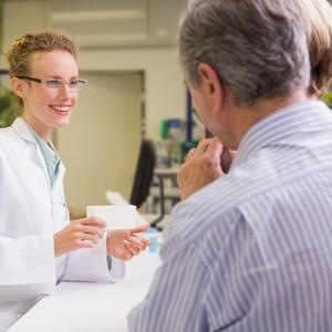 vrouwelijke apotheker praat met ouder echtpaar