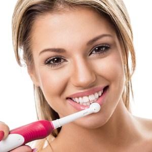 femme avec une brosse à dents électrique