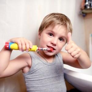 garçon avec une brosse à dents électrique