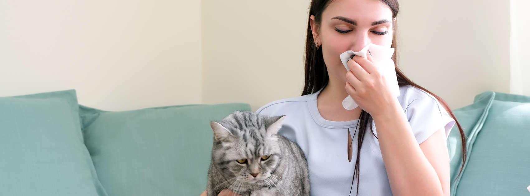 une jeune femme éternue d'allergie à son chat.
